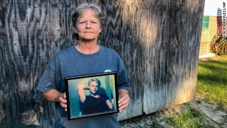 """Sandy Smith holds a photo of her late son, Stephen Smith, in June. """"There will never be another like him,"""" he said."""