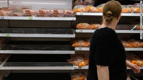 A woman walks past empty shelves that stock chicken at an Asda supermarket on September 19, 2021, in London.