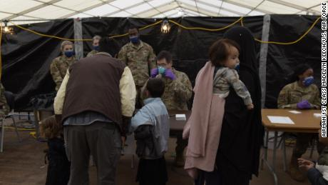 US Air Force Airmen evaluate evacuees waiting to be vaccinated with the measles, mumps, and rubella and varicella vaccines at Ramstein Air Base.