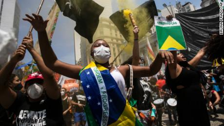 A woman draped in the Brazilian national flag raises slogans during a protest against Brazilian President Jair Bolsonaro on Saturday, October 2.