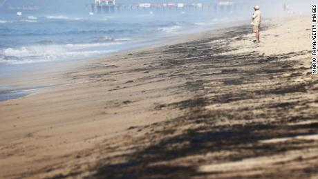 A person stands Sunday near oil washed up on Huntington State Beach in California.