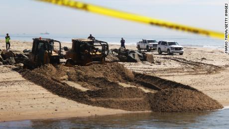 A cleanup crew works near Huntington State Beach in California.