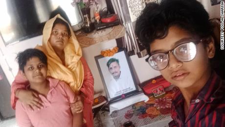 पूजा शर्मा और उनके बच्चे अपने दिवंगत पति की तस्वीर के सामने घर पर हैं, जिनकी अप्रैल में दिल्ली, भारत में कोविड -19 से मृत्यु हो गई थी।