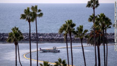 A boat checks on one of two oil containment booms at the entrance to Newport Harbor in Newport Beach Wednesday.