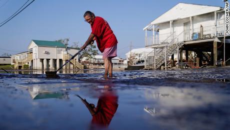 सिंडी रोजस सितंबर में तूफान इडा के बाद, लुइसियाना के लाफिटे में अपने ड्राइववे से कीचड़ और बाढ़ के पानी को साफ करती है।