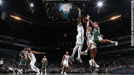 Bucks' Justin Robinson drives into the basket during a preseason game against the Nets.