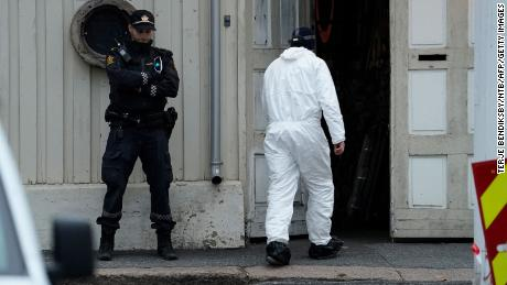 A police investigator passes a Norwegian policeman standing guard Thursday as investigations continue into the deadly bow-and-arrow attack in Kongsberg, Norway.