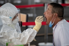A Beijing resident is tested for COVID-19 last week, after several new domestic cases were reported in the Chinese capital. (Photo by Nicolas Asfouri/AFP via Getty Images)