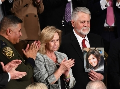 Carl and Marsha Mueller, among the special guests at President Trump's State of the Union address on February 4, 2020, hold up a picture of their daughter, Kayla. (Photo by B