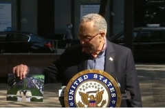 Two masked pedestrians look over at unmasked Sen. Chuck Schumer as he stands on a New York City sidewalk and displays a photo of the White House ceremony announcing the Supreme Court nomation of Amy Coney Barrett. (Screen Capture)