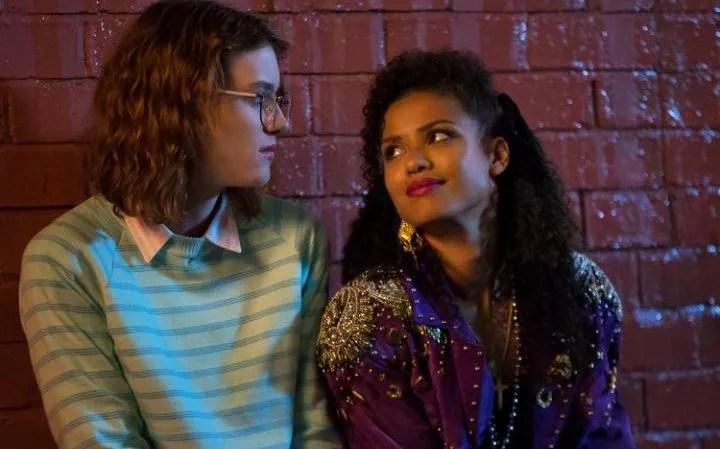 Imagen de un fotograma del capítulo donde las dos chicas protagonistas charlan frente a un muro de ladrillo donde se resguardan de la lluvia.