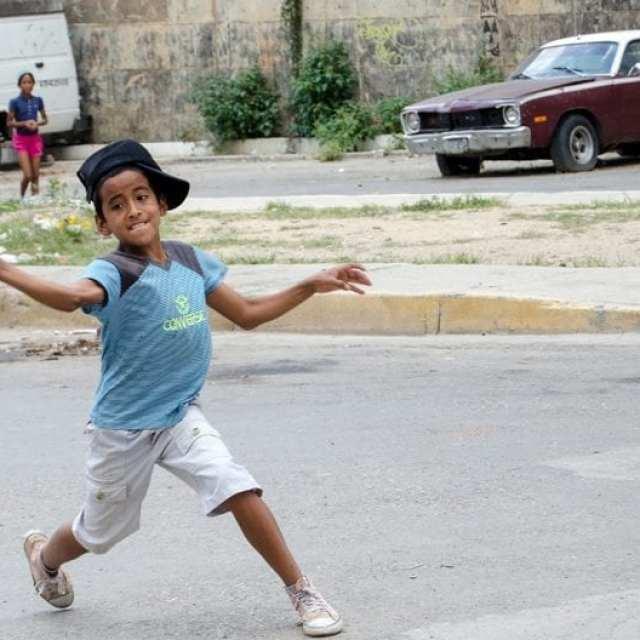 Niño jugando pelotica de goma