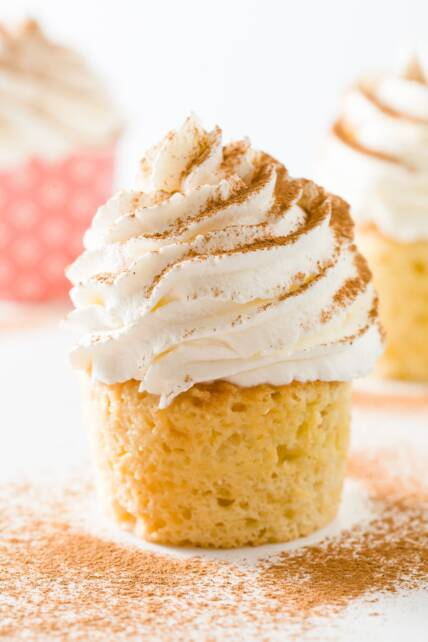 Close up of a tres leches cupcake with a couple other cupcakes in the background