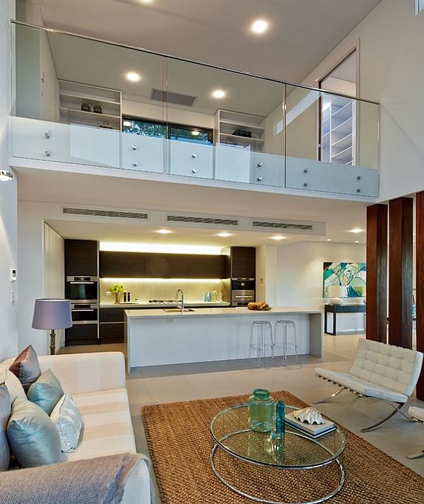 Sala de estar contemporánea en blanco con valla de vidrio para la entreplanta