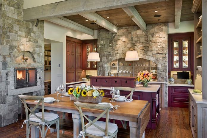 Exquisite eat-in kitchen with fireplace, purple cabinets and stone walls