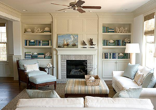 living rooms - white sofas blue pillows yellow blue striped ottoman chair blue cushions bamboo roman shades built-ins shelves cabinets fireplace