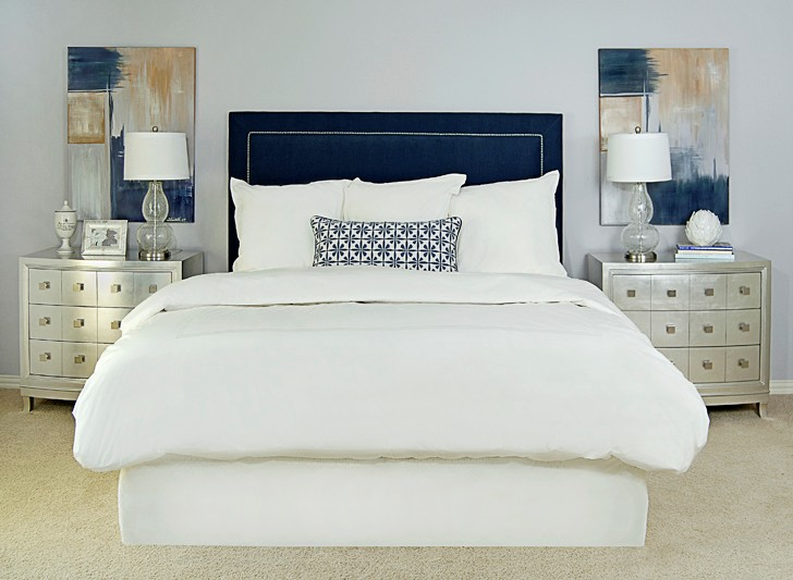 EJ Interiors - bedrooms - Upholstered blue headboard with nailheads, abstract art, metallic nightstands, navy, gray, purple, geometric pillow, white bedding, gray-purple walls, Restoration Hardware bedding, Home Goods lamps, artichoke accessory, king bed, silver nightstands,