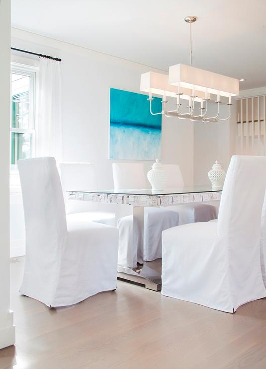 Glass And Chrome Dining Table With White Slipcovered Chairs