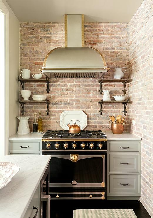 Stainless Steel Dome Kitchen Hood With Brass Trim And A Black And Gold Lacanche Range