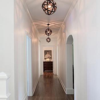 Long White Hallway With Armillary Sphere Pendants