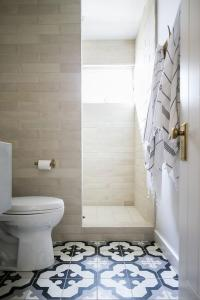 White And Black Striped Porcelain Floor Tiles Design Ideas Chic transitonal bathroom features black and gray mosaic floor tiles  leading past a white porcelain toilet to a cream stacked tiles mounted  framing a