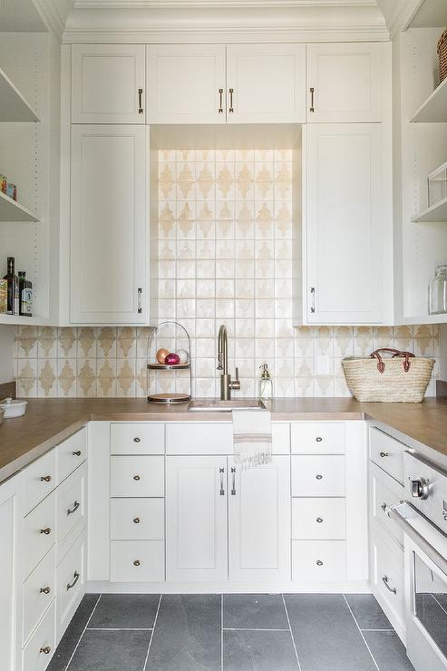 white and tan kitchen pantry with slate