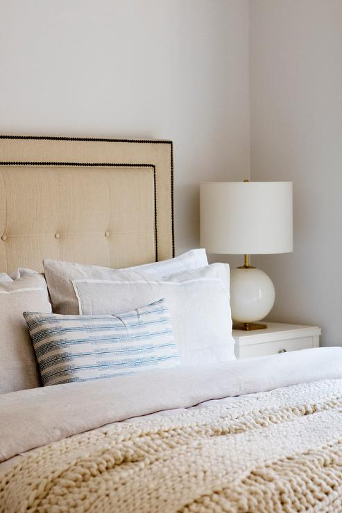 tan upholstered bed with white and gold