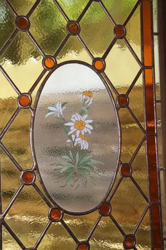 Jussara aponta para os vitrais que têm a flor Edelweiss em seu centro