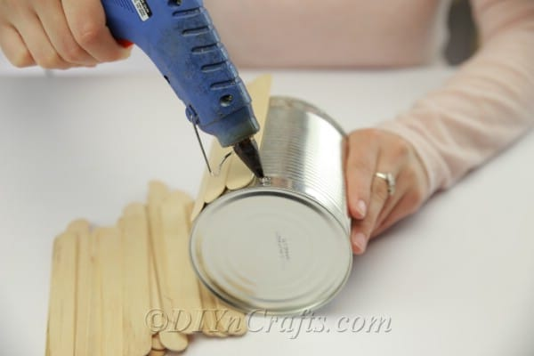 Gluing popsicle sticks onto the outside of the empty can