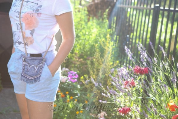 Woman standing by a flower garden wearing the denim purse with rope strap