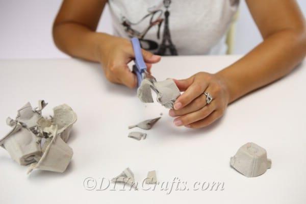Cutting apart an egg carton to create a halloween monster