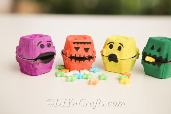 Halloween monster treat boxes lined up on a tan counter with candy in front