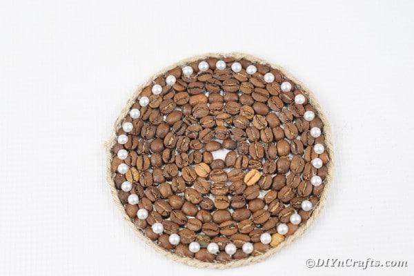 Coffee bean coaster on white surface