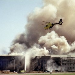 A helicopter flies over the Pentagon in Washington, Tuesday, Sept. 11, 2001 as smoke billows over the building. The Pentagon took a direct, devastating hit from an aircraft and the enduring symbols of American power were evacuated as an apparent terrorist attack quickly spread fear and chaos in the nation's capital. (AP Photo/Heesoon Yim)