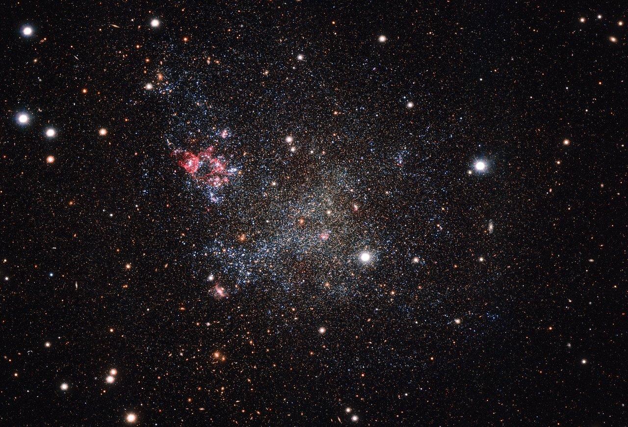 Esta imagen, captada con la cámara OmegaCAM (instalada en el Telescopio de rastreo del VLT de ESO, en Chile) muestra una pequeña galaxia inusualmente limpia. IC 1613 contiene muy poco polvo cósmico, permitiendo a los astrónomos explorar su contenido con gran facilidad.