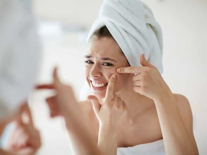 woman looking at acne zit in mirror