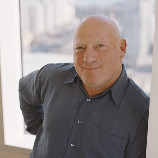bald man smiling at the camera, wearing a blue shirt with a window and cityscape behind him