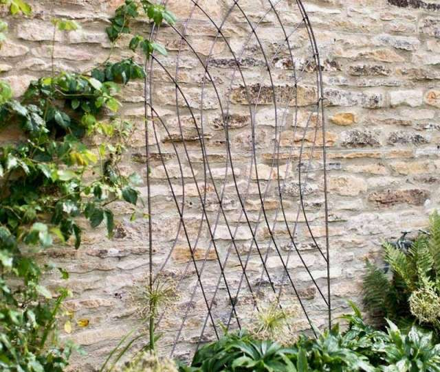A Raw Metal Barrington Arch Trellis Comes With Spikes To Secure It To The Ground