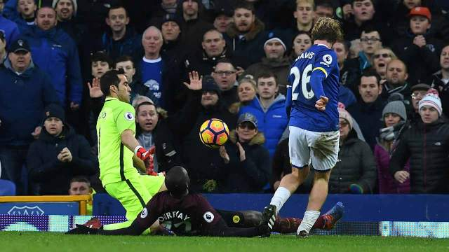 Everton's English midfielder Tom Davies (R) chips the ball past Manchester City's Chilean goalkeeper Claudio Bravo to score their third goal during the English Premier League football match between Everton and Manchester City at Goodison Park in Liverpool, north-west England on January 15, 2017. PHOTO: Paul ELLIS / AFP