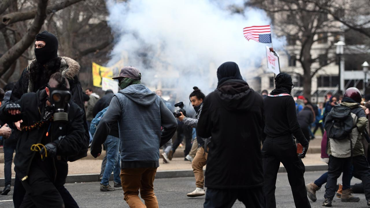 Anti-Trump protesters flee as police flash-bang grenade explodes during clashes in Washington, DC, on January 20, 2107. Masked, black-clad protesters carrying anarchist flags smashed windows and scuffled with riot police Friday in downtown Washington, blocks away from the route of the parade in honor of newly sworn-in President Donald Trump. Washington police arrested more than 90 people over acts of vandalism committed on the fringe of peaceful citywide demonstrations being held against Trump's inauguration. Jewel SAMAD / AFP