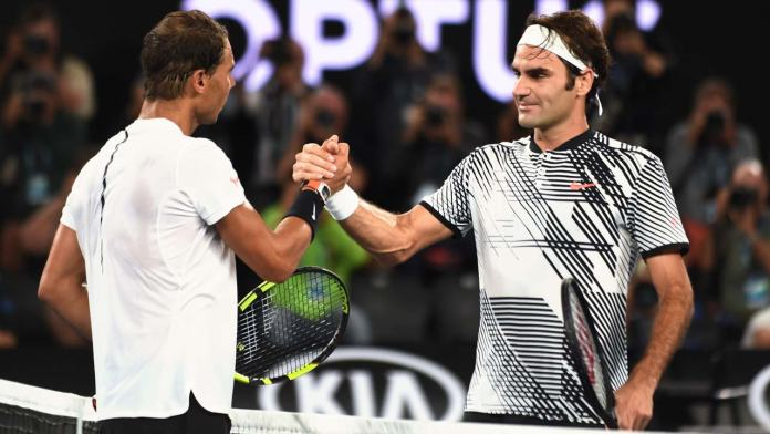 Switzerland's Roger Federer (R) is congratulated by Spain's Rafael Nadal after winning their men's singles final match on day 14 of the Australian Open tennis tournament in Melbourne on January 29, 2017.  PAUL CROCK / AFP