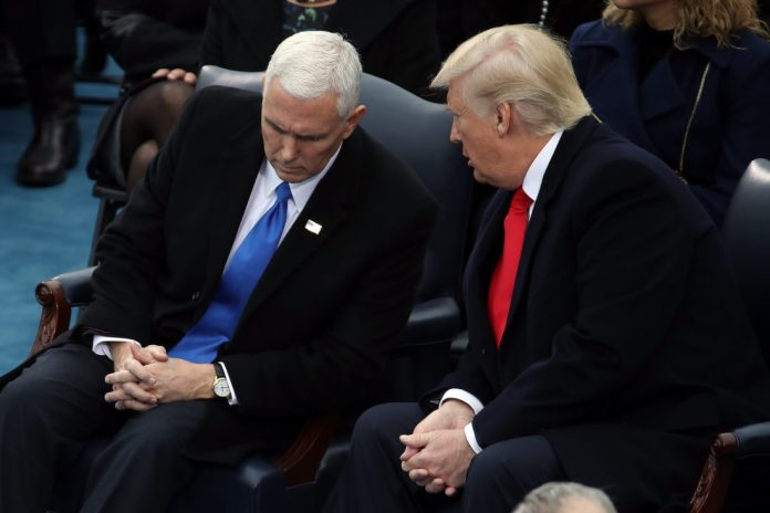 U.S. President-elect Donald Trump (R) speaks to Vice President-elect Mike Pence on the West Front of the U.S. Capitol on January 20, 2017 in Washington, DC. In today's inauguration ceremony Donald J. Trump becomes the 45th president of the United States.   Drew Angerer/Getty Images/AFP