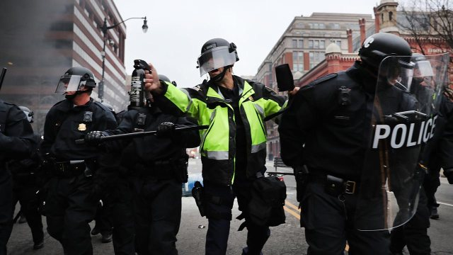 A police officer holds a tear gas cannister as police and demonstrators clash in downtown Washington after a limo was set on fire following the inauguration of President Donald Trump on January 20, 2017 in Washington, DC. Washington and the entire world have watched the transfer of the United States presidency from Barack Obama to Donald Trump, the 45th president. Spencer Platt/Getty Images/AFP. SPENCER PLATT / GETTY IMAGES NORTH AMERICA / AFP