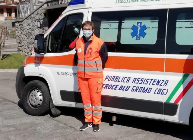 Paola a fianco dell'ambulanza su cui presta servizio come volontaria quando non è in ospedale