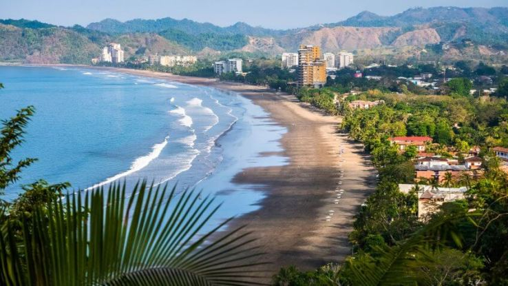 Tropical wide sandy beach of the town of Jaco, Costa Rica.
