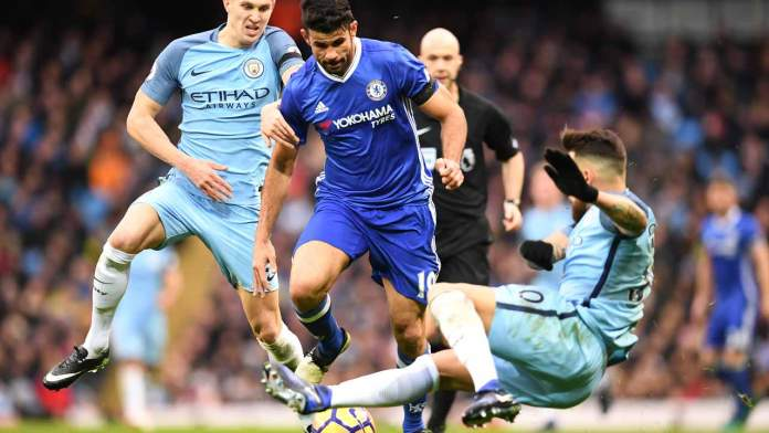 Chelsea's Brazilian-born Spanish striker Diego Costa (C)v ies with Manchester City's English defender John Stones (L) and Manchester City's Argentinian defender Nicolas Otamendi during the English Premier League football match between Manchester City and Chelsea at the Etihad Stadium in Manchester, north west England, on December 3, 2016.  Paul ELLIS / AFP