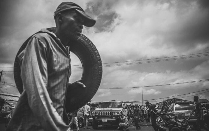 Man with tire walking PHOTO: Seun O