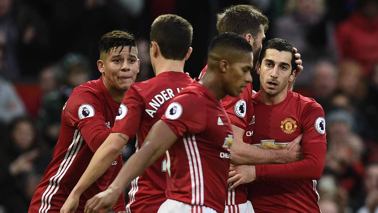 Manchester United's Armenian midfielder Henrikh Mkhitaryan (R) celebrates with teammates after scoring the opening goal of the English Premier League football match between Manchester United and Tottenham Hotspur at Old Trafford in Manchester, north west England, on December 11, 2016. OLI SCARFF / AFP