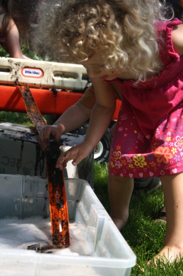preschooler driving muddy car down hot wheels track into basin of soapy water