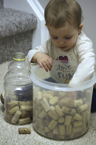 Baby dropping corks into a jug to develop fine motor skills